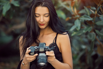 Attractive woman photographer taking images with dslr camera outdoors in park. Gorgeous happy mixed race Asian Caucasian female enjoying traveling outdoors during holidays in Europe.