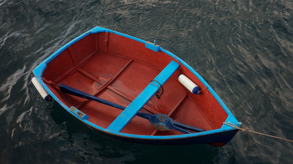 Small wooden fishing boat with a single blue oar inside, tied up near a pier isolated against dark, murky ocean water in Los Abrigos, Tenerife, Canary Islands, Spain