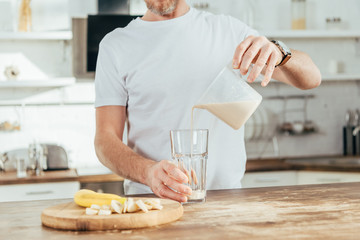 cropped shot of adult man pouring banana protein shake in glass at home