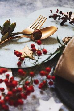 christmas table setting, golden cutlery and nandinas