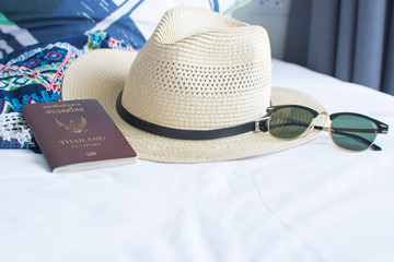 passport, hat, and sunglasses on withe bed, accessories for the trip. soft focus.