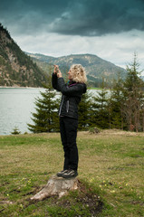 Young blonde woman takes a picture in front of mountain panorama with her smartphone