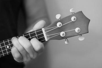 Men hand plaiyng  on ukulele macro black and white