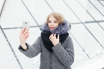 Selfie time, Young funky blogger is making photo for her social networks page. Young happy woman taking selfie. Cold sunny weather. Woman winter concept.