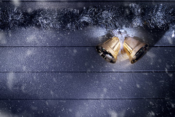 close up view  of  two golden bells  on snowbound  wooden back