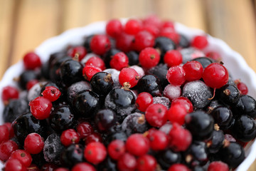 Frozen mixed berries as background. Currant mulberry texture pattern. Diet vegetarian food in winter.