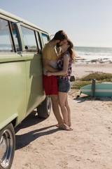 Couple kissing at van on beach