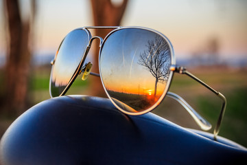 Sunglasses with sunset reflections on a bike seat Wall mural