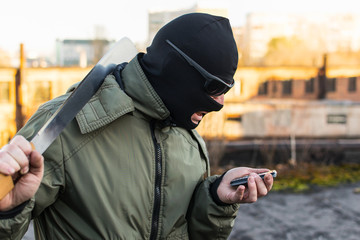 Criminal in a mask in a rage looks at the phone