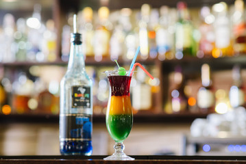 a Three colors cocktail in glass at the bar background