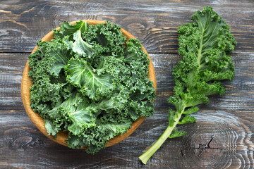 Fresh green curly kale leaves on a wooden table. selective focus. rustic style. healthy vegetarian food