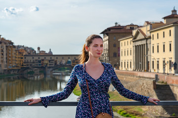 Romantic young beautiful girl in ancient city center, Florence, Tuscany, Italy. Outdoor female portrait over varicoloured beautiful building in old European town.