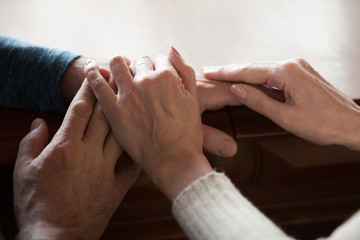 Close up of caring aged wife caressing husband hands showing love and support, romantic senior couple touching comforting each other, elderly man and woman enjoying tender moment at home together
