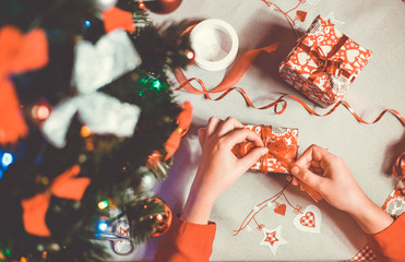 Hands of young woman wrapping some presents / gifts to beautiful stylish christmas paper with a red ribbon, celebration concept (color toned image)