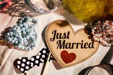 """Scritta """"Just Married"""" su cuore di carta e vari accessori come collane e parrucche per Photo Booth"""