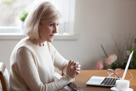 Thoughtful aged woman working at laptop thinking or considering something, doubtful senior female feel unsure pondering about solution, elderly lady sit at table lost in thoughts making decision