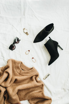 Flat lay, top view fashion concept. Trendy woman clothes and accessories on white blanket.