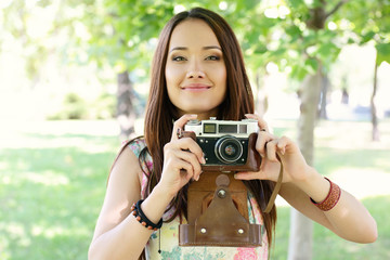 Cheerful beautiful girl talks pictures with vintage camera in summer park. Young woman photographer posing outdoor with her camera