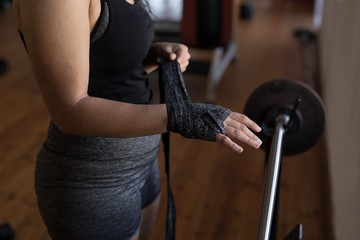 Female boxer wearing hand wrap in fitness studio