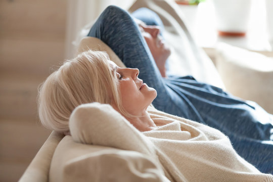 Close up of peaceful aged couple lying with eyes closed relaxing on cozy sofa, calm senior husband and wife nap on couch at home seeing dreams, elderly man and woman rest spending weekend indoors