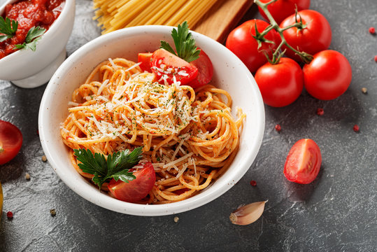 Pasta, spaghetti with tomato sauce in white bowl on grey background. Copy space.