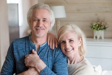 Portrait of happy senior couple posing for family picture at home, smiling elderly wife leaning on caring husband holding hands looking at camera during photoshoot, aged man and woman shoot embracing