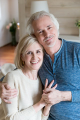 Portrait of smiling aged husband and wife embracing making family picture at home, happy senior couple hugging and holding hands looking at camera shooting for anniversary album photo