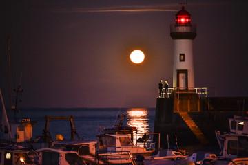 Un couple une lune et un phare