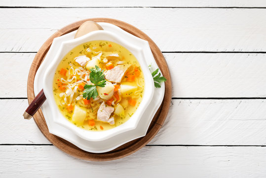 Chicken soup with noodles and vegetables in white bowl on white  wooden background