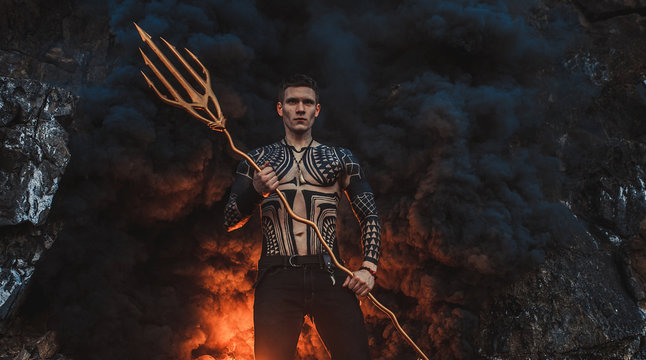 A young man with a trident against the background of fire and smoke.
