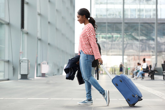 side portrait of young black woman walking with suitcase in airport