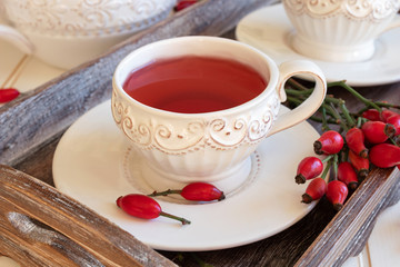 Rosehip tea in white vintage cups with fresh rosehips