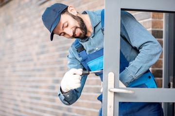 Builder in uniform installing a door lock into the entrance door of a new house outdoors