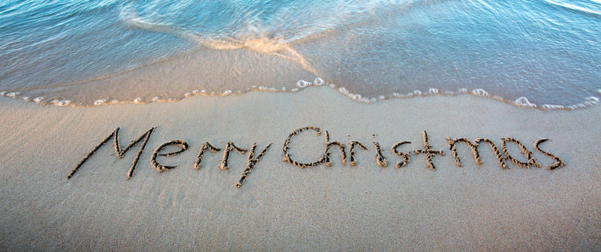 Word Merry Christmas written on the sand near the sea.