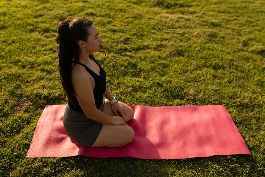 Female jogger doing yoga in the park