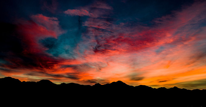 Aerial, drone view of sunset above Tubac, Arizona with mountin silhouettes and beautiful colors