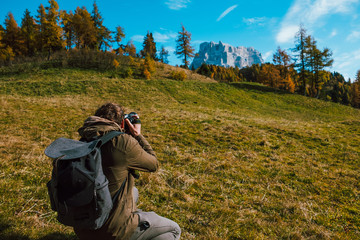 young adventure explorer and photographer tourist taking landscape picture of pelmo mountain in alps dolomites in autumn sunny day