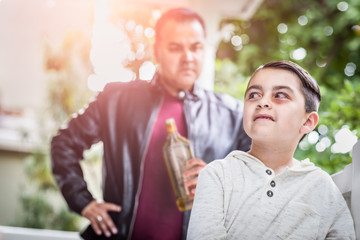 Afraid and Bruised Mixed Race Boy In Front of Angry Man Holding Bottle of Alcohol