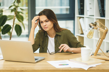 Feeling tired and stressed. Frustrated young woman with headache sitting at her working place in office, using laptop. Wall mural