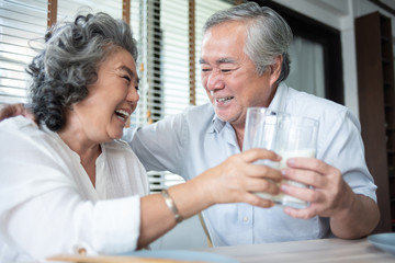 Happy Asian Senior Couple laughing and drinking milk.
