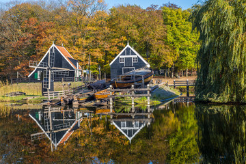 Historic Dutch scene with an old shipyard, wooden barn and water windmill in the open air museum in Arnhem in the Netherlands