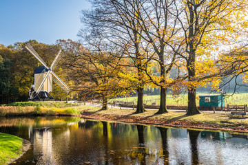 Historic Dutch scene with  wooden barn and water windmill in the open air museum in Arnhem in the Netherlands