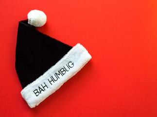 black and white fur pompom hat with the words Bah Humbug on the brim isolated on a red background with copy space