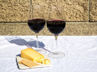 two glasses of red wine with cheese and crackers on a white linen cloth next to a stone wall