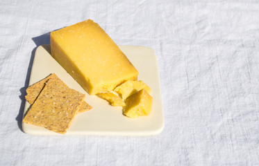 small plate with a wedge of cheddar cheese and crackers on a white linen tablecloth with copy space