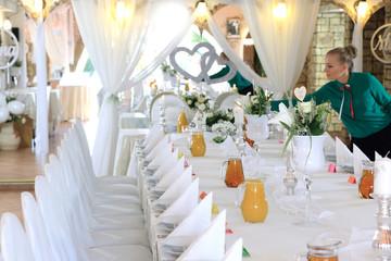 Obraz Kelnerka dekoruje stół w restauracji nakryty białym obrusem, ślub, wesele. - fototapety do salonu