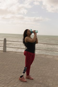 Disabled woman drinking water on promenade