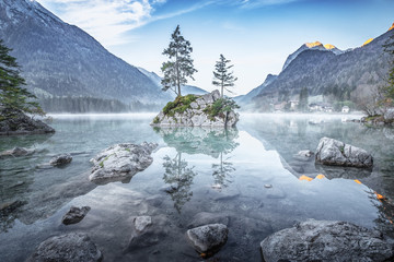 Hintersee - Awesome Lake landscape in Germany, Europe. Majestic blue our scene before the sunrise. Lovely stones at foreground, island with two lonely pine trees. Epic mountains in background.