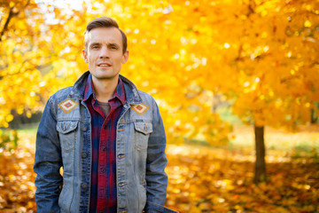 Photo of young man in autumn park