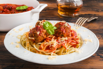 Pasta and meatballs with tomato sauce, white casserole and plate on wooden rustic table